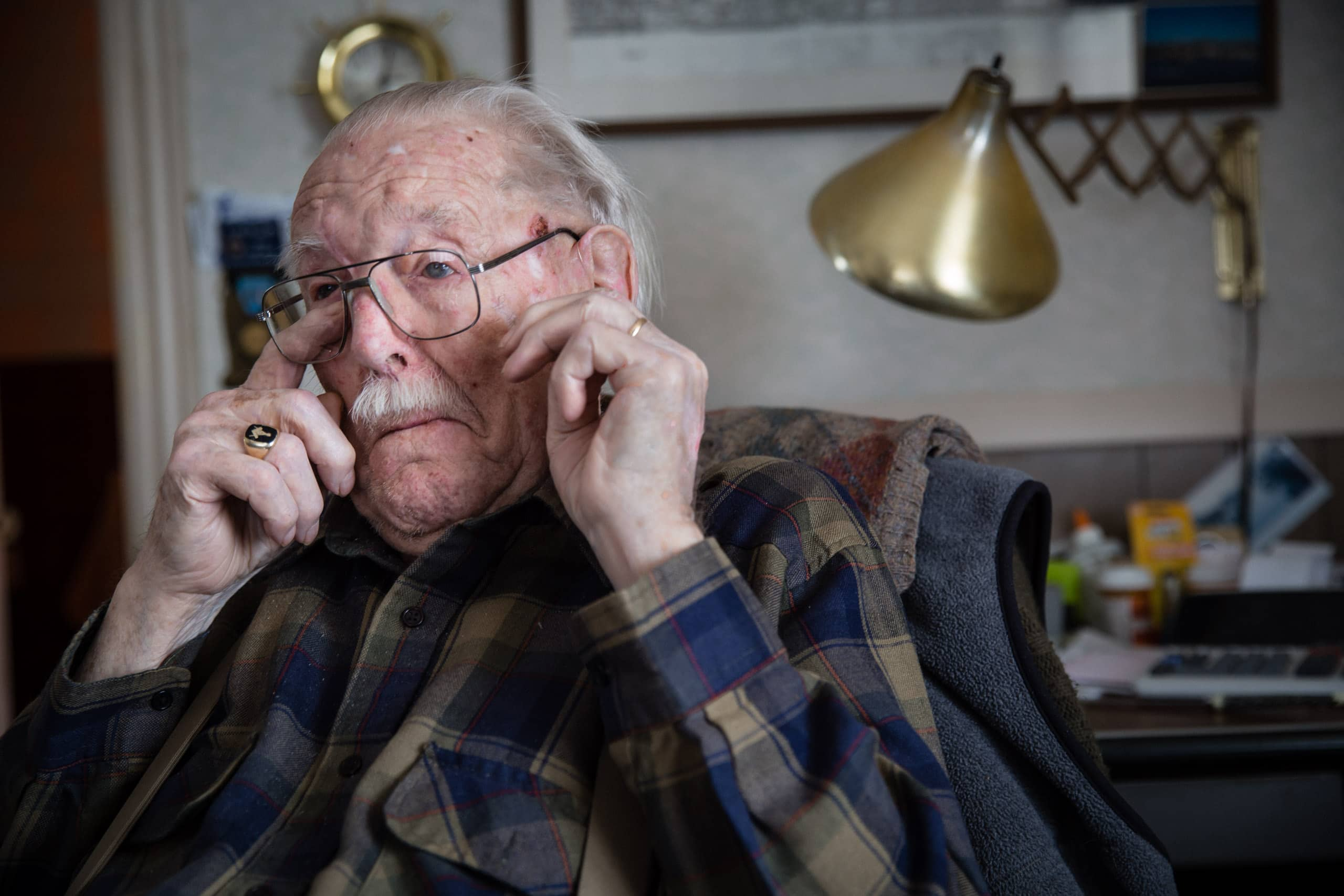 A medium close up portrait of a 100 year old man wiping a tear from his right eye. TThis photograph is part of the To Live 10,000 Years series by Danny Goldfield.