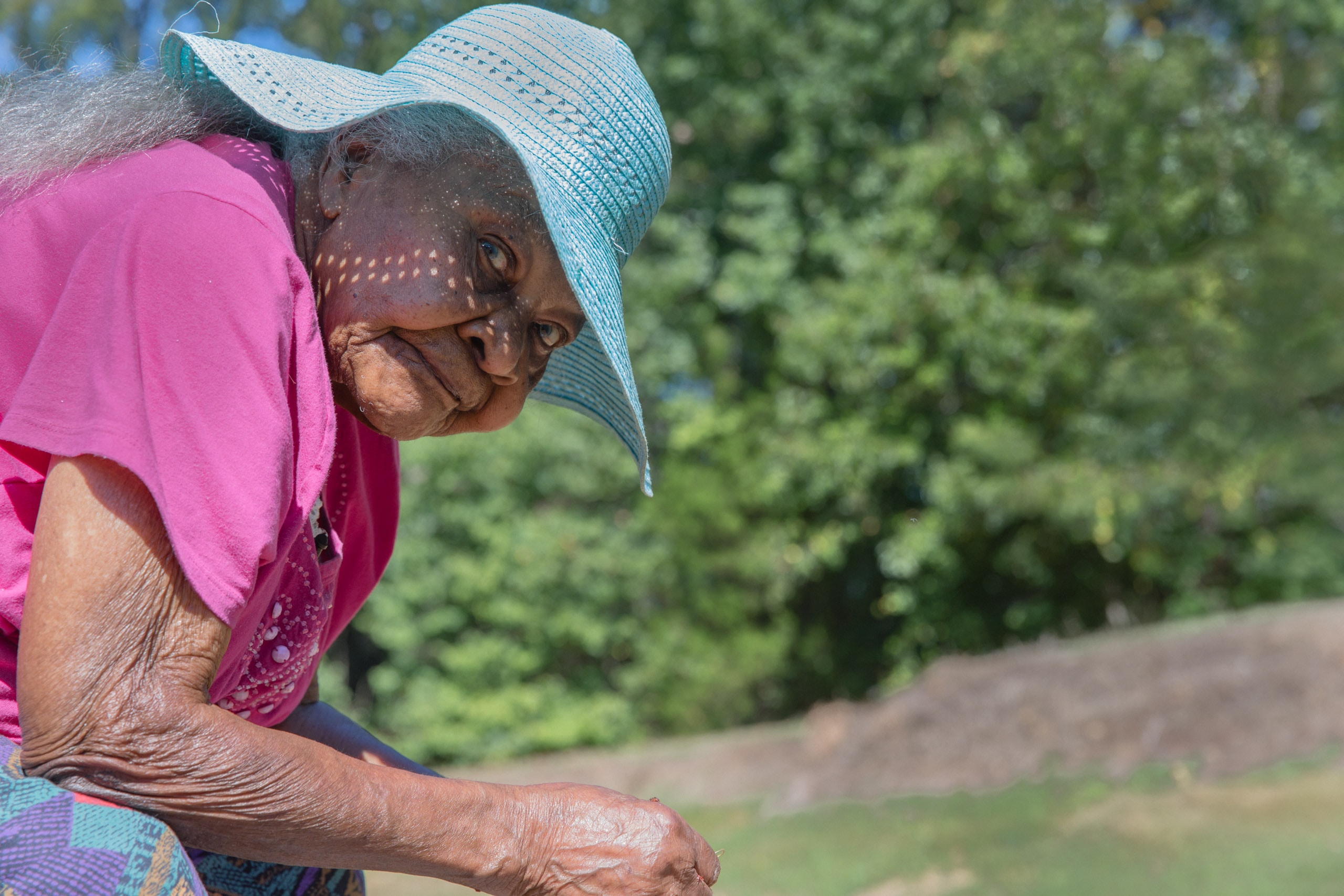 Medium close up of a 100 year old woman outside wearing a light blue sun hat and pink shirt. She is sitting perpendicular to the camer and has her head tirned to the camera lens. She has acurious and relaxed look on her face. Her eyes are light blue like her hat. This photograph is part of the To Live 10,000 Years series by Danny Goldfield.