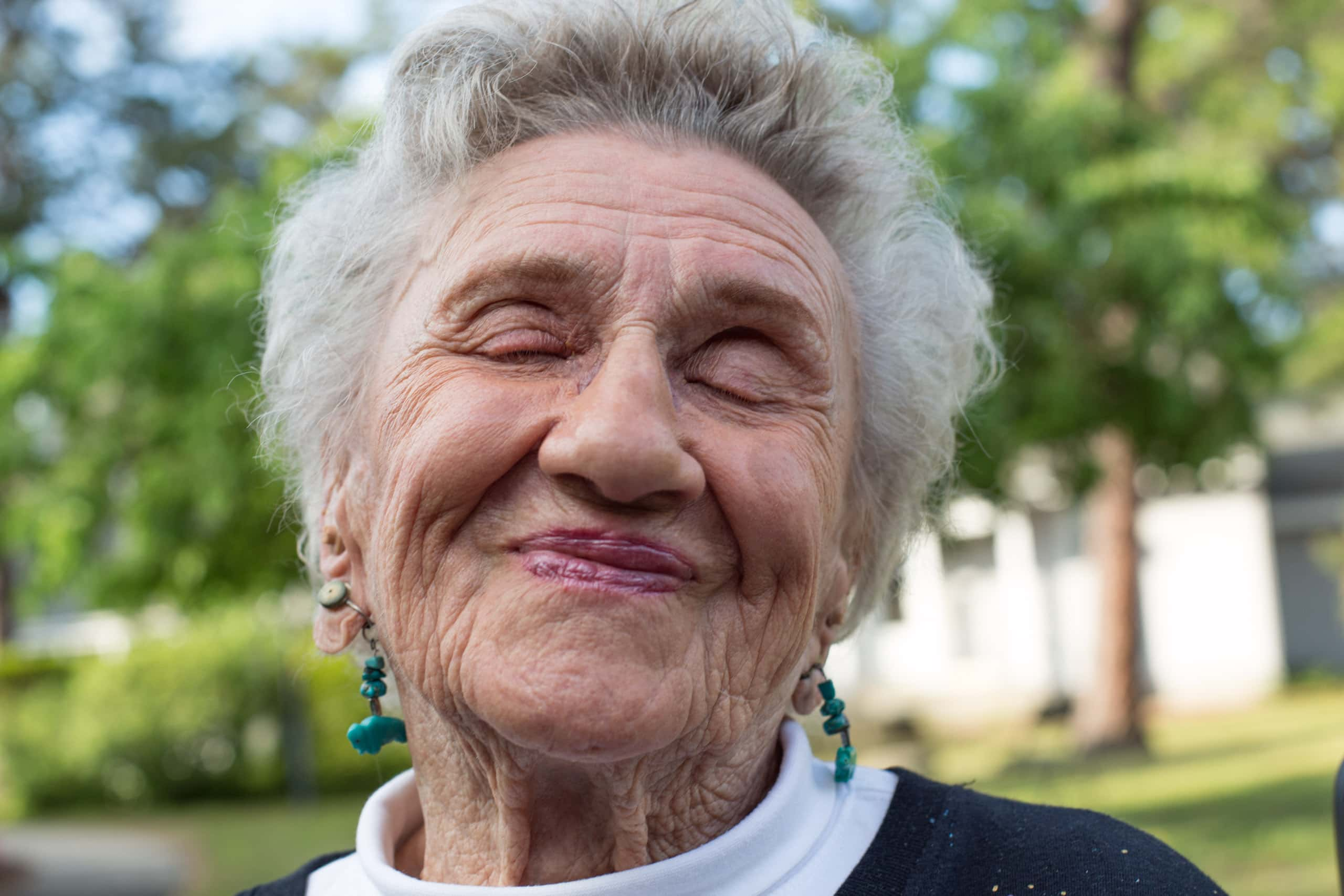 A close up portrait of a 102 year old woman with her eyes closed and smile. This photograph is part of the To Live 10,000 Years series by Danny Goldfield.